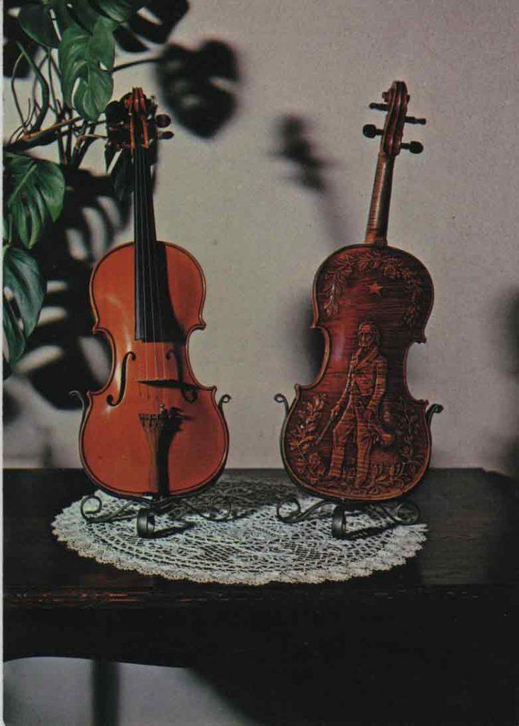 Indexation : Violons Mirecourt##Légende : Violons fait à Mirecourt vers 1870.##A droite fond sculpté représentant le célèbre violoniste italien## Nicollo Paganini né à Gênes (1782 à 1840)##Editeur : La Cigogne##Epoque : Moderne##Propriété : Art-003-mdv
