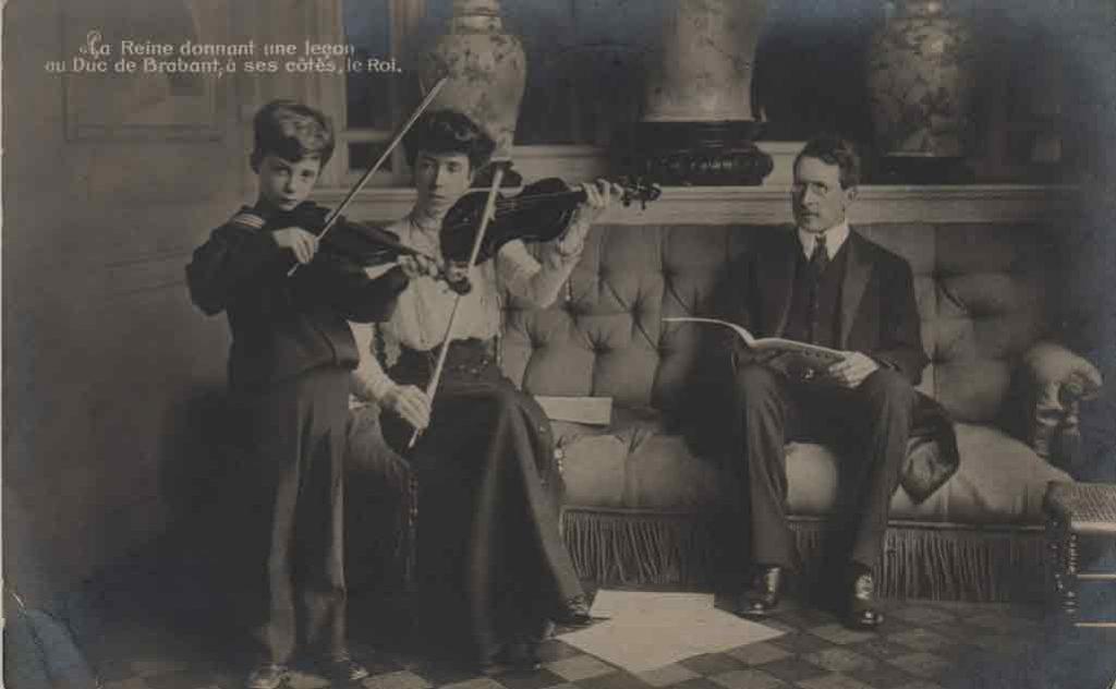 """Indexation : Leçon de violon##Légende : """"La reine donnant une leçon au Duc de Brabant,##à ses côtés, le Roi.""""##Editeur : V. G., Bruxelles, n° 28##Epoque : Ancienne##Date : 1911 (affranchissement)##Propriété : Gem-033-mdv"""