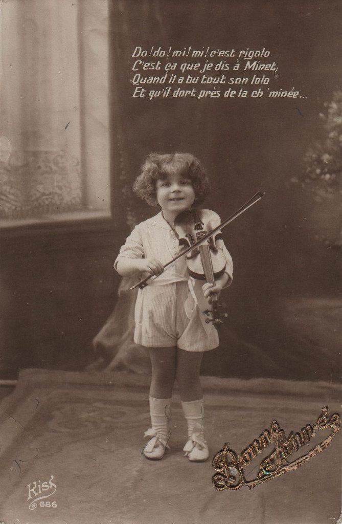 """Indexation : Fillette violoniste##Légende : """"Do ! Do ! Mi ! Mi ! C'est rigolo##C'est ça que je dis à Minet##Quand il a bu tout son lolo##Et qu'il dort près de la ch'minée...""""##Editeur : Kiss 686##Epoque : Ancienne##Propriété : Enf-022-mdv"""