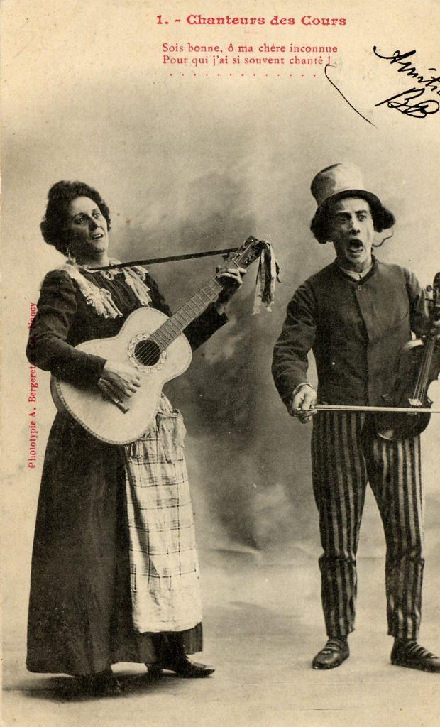 """Indexation : Violoniste et guitariste-chanteuse##Légende : """"Chanteurs des cours##Sois bonne, ô,ma chère inconnue,##Pour qui j'ai souvent chanté !""""##Editeur : Phototype, A. Bergeret et Cie, Nancy##Epoque : Ancienne##Propriété : Por-004-mdv"""